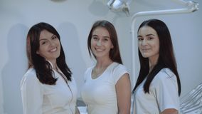 Portrait of happy, confident dentists look at camera at dental room stock video