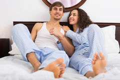 Portrait of happy couple awake in bed. Young adults posing in family bed and smiling Stock Photography