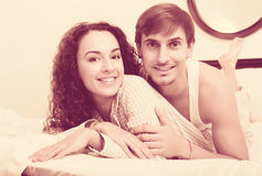 Portrait of happy couple awake in bed. Young adults posing in family bed and smiling Stock Photo