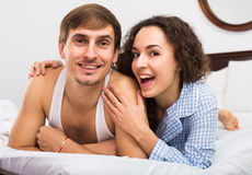 Portrait of happy couple awake in bed. Young adults posing in family bed and smiling Stock Image