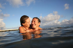 Portrait of a happy couple bathing and hugging in the sea Stock Photos