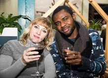 Portrait of happy couple: black man and white woman with glass of wine Royalty Free Stock Image
