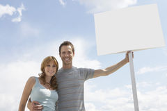 Portrait of happy couple with blank sign board against cloudy sky Stock Photo