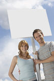 Portrait of happy couple with blank sign over cloudy sky Royalty Free Stock Photography