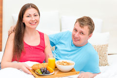 Portrait of a happy couple with breakfast. On a tray Royalty Free Stock Photography