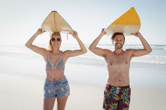 Portrait of happy couple carrying surfboard at beach Stock Images