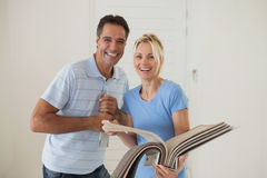 Portrait of a happy couple with color book in new house Royalty Free Stock Photo