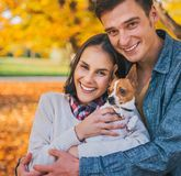Portrait of happy couple with dog outdoors in autumn Stock Photo