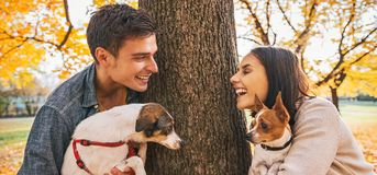 Portrait of happy couple with dogs outdoors in autumn park. Portrait of happy young couple with dogs outdoors in autumn park Royalty Free Stock Photography