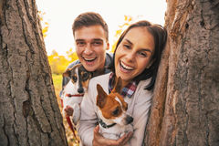 Portrait of happy couple with dogs outdoors in autumn park Stock Photo