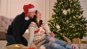 Portrait of Happy Couple. They Are Doing Selfie and Smiling Together. Happy New Year and Merry Christmas Concept. HD, Fun, Love, Christmas Tree, Santas Hats stock video footage
