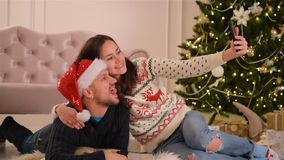 Portrait of Happy Couple. They Are Doing Selfie and Smiling Together. Happy New Year and Merry Christmas Concept. HD, Fun, Love, Christmas Tree, Santas Hats stock video