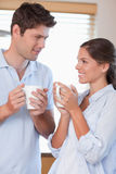 Portrait of a happy couple drinking coffee. In their kitchen Royalty Free Stock Image