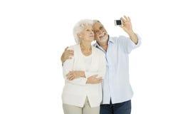 Portrait of happy couple of elderly. Elderly couple taking photograph  on white background isolated Royalty Free Stock Photo