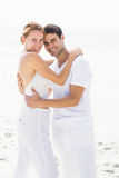 Portrait of happy couple embracing each other on the beach Stock Images