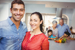 Portrait of happy couple with family preparing food in background Royalty Free Stock Photos