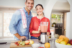Portrait of happy couple with fruit juice Stock Images