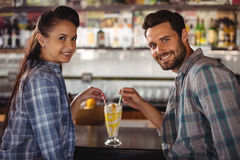 Portrait of happy couple having milkshake at counter. In restaurant Stock Photography