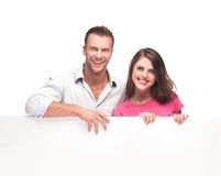 Portrait of a happy couple holding blank billboard. Portrait of a happy couple holding a blank billboard on white background royalty free stock images