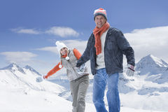 Portrait of happy couple holding hands on snowy mountain stock photo