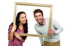 Portrait of happy couple holding picture frame Royalty Free Stock Images