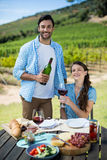 Portrait of happy couple holding red wine bottle and glass Royalty Free Stock Image