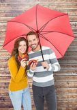 Portrait of happy couple holding umbrella and maple leaves Royalty Free Stock Image