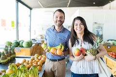 Cheerful Couple Buying Fresh Fruits Together In Supermarket royalty free stock photos