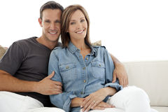 Portrait of a happy couple at home. Portrait of a Caucasian heterosexual couple sitting on a sofa at home Stock Images