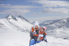 Portrait of happy couple hugging on snowy mountain Stock Photo