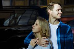 Portrait of a happy couple hugging in the street, in the city.standing in better from the sun.date.the sun shines on the faces, co. Uple faces in the sun, a kiss royalty free stock image