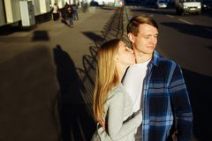Portrait of a happy couple hugging in the street, in the city.standing in better from the sun.date.the sun shines on the faces,. Couple faces in the sun, a kiss royalty free stock image