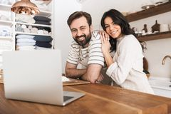 Portrait of happy couple looking at laptop while cooking pastry in kitchen at home. Portrait of happy couple men and women 30s wearing aprons looking at laptop stock image