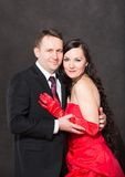Portrait of happy couple in love posing at studio on gray background dressed in red. Royalty Free Stock Image