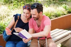 Happy couple with luggage and travel book sitting outside Royalty Free Stock Photos