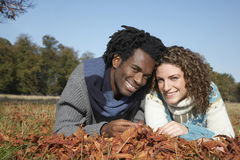 Portrait Of Happy Couple Lying In Field Royalty Free Stock Image