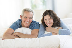 Portrait Of Happy Couple Lying Together In Bed Royalty Free Stock Images