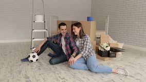Portrait of a happy couple in a new apartment. Portrait of a happy young couple in plaid shirts in a new apartment among cardboard boxes. Young couple moving in stock video
