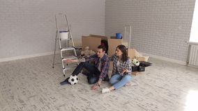 Portrait of a happy couple in a new apartment. Young couple are sitting on the floor in a new apartment and together make up a plan. Couple moving into new stock video
