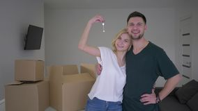 Portrait of happy couple new home owners show keys to flat and hug while relocation on background of boxes stock video footage