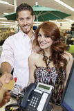 Portrait of a happy couple paying through credit card Royalty Free Stock Photography