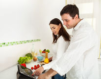 Portrait of a happy couple preparing food Stock Photography