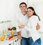 Portrait of a happy couple preparing food. And drinking white wine in the kitchen Stock Images