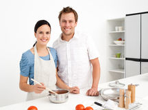 Portrait of a happy couple preparing sauce Royalty Free Stock Photography
