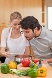 Portrait of a happy couple preparing a sauce royalty free stock photography