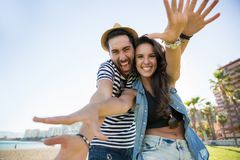 Happy couple raising hands in front of them laughing Stock Photos