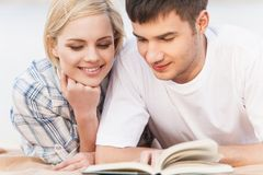 Portrait Of Happy Couple Reading Book On Summer Beach. Stock Images