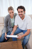 Portrait of a happy couple reading a letter. In their living room Royalty Free Stock Photo