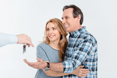 Portrait of happy couple receiving keys from new house Royalty Free Stock Photo