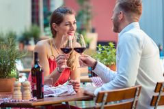 Young couple having red wine at restaurant. Portrait of a happy couple at restaurant toasting glass of red wine stock photo